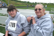 Spectators sitting on a bench at a track and field event